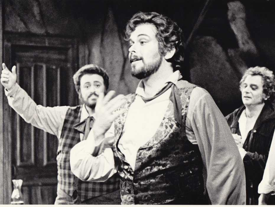 Patrick Raftery in a production of La Bohème, singing in the foreground as Luciano Pavarotti looks on in the background.