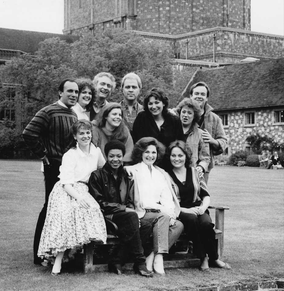 Patrick Raftery smiling with 11 other young singers in front of a school in Glyndebourne. The other singers include Dale Duesing, Ashley Putnam, Richard Stilwell, Gianna Rolandi, Dennis Bailey, Carol Vaness, Faith Esham, Cynthia Clarey, Regina Sarfaty, Delores Ziegler and Mimi Lerner.