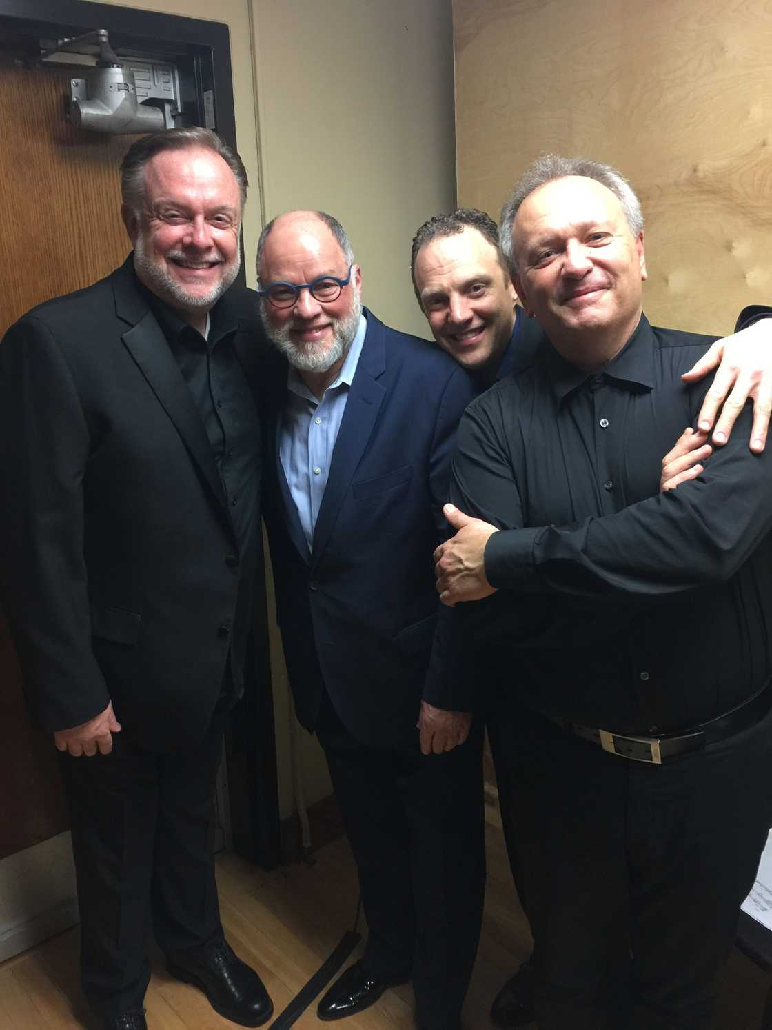 Patrick Raftery smiling with Eric Wilson, Jasper Wood and Mark Anderson as they all stand in a backstage hallway wearing black suits after a performing a concert at the University of British Columbia.